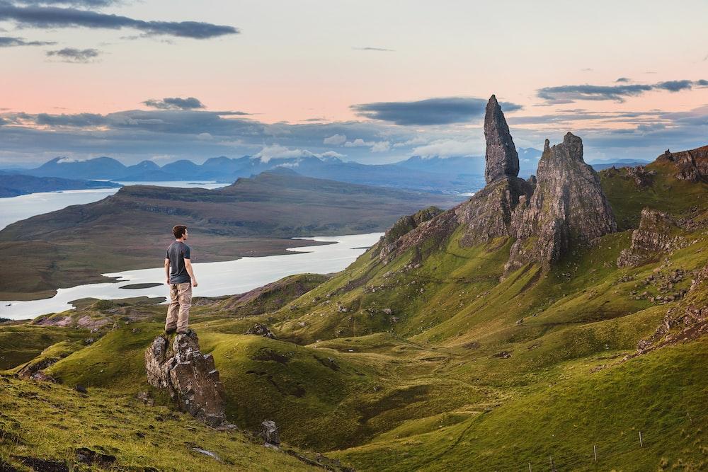 man standing wearing grey shirt and brown pants facing rocky mountain