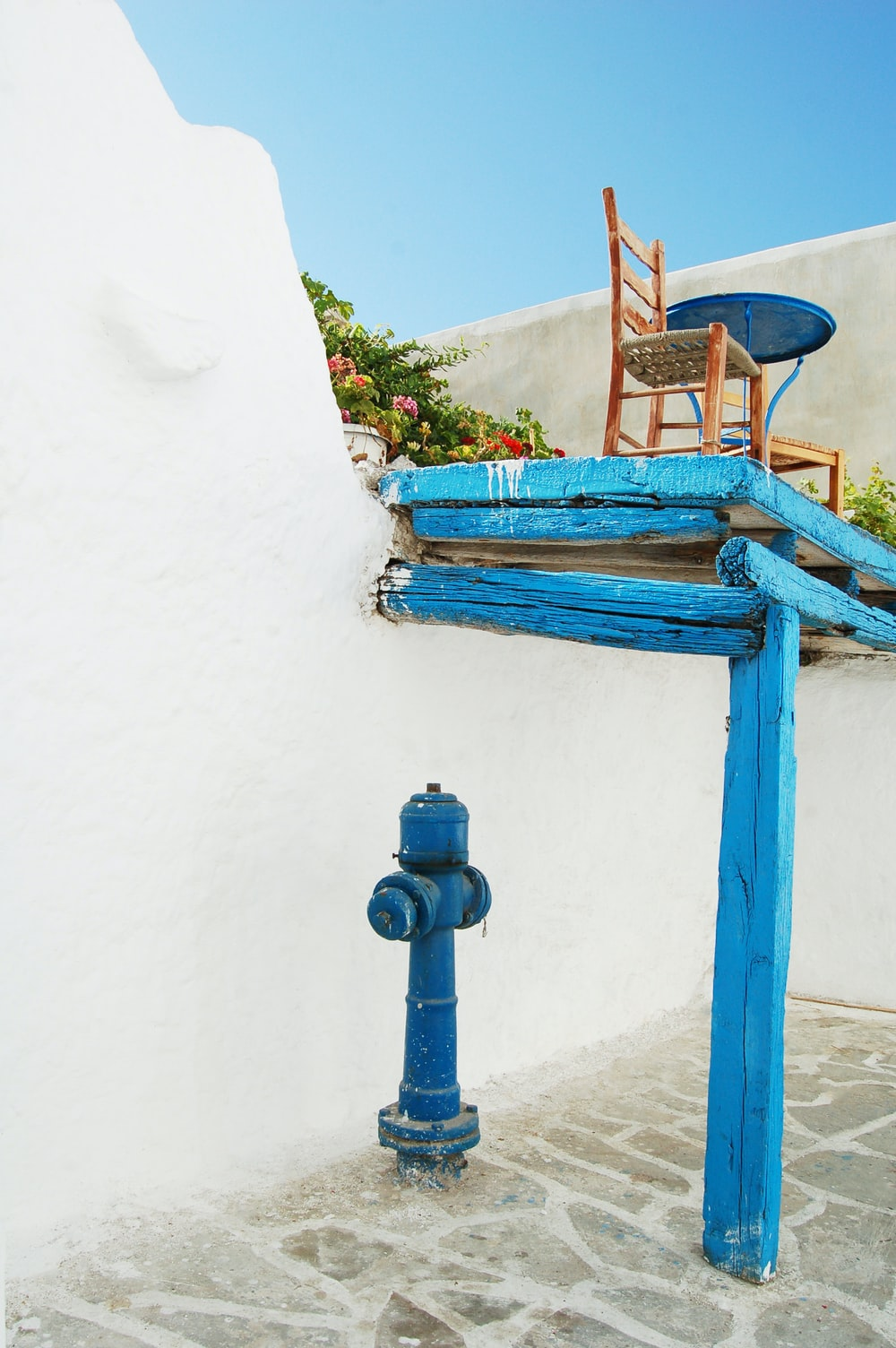 blue hydrant under blue wooden loft with chair on top under blue sky at daytime