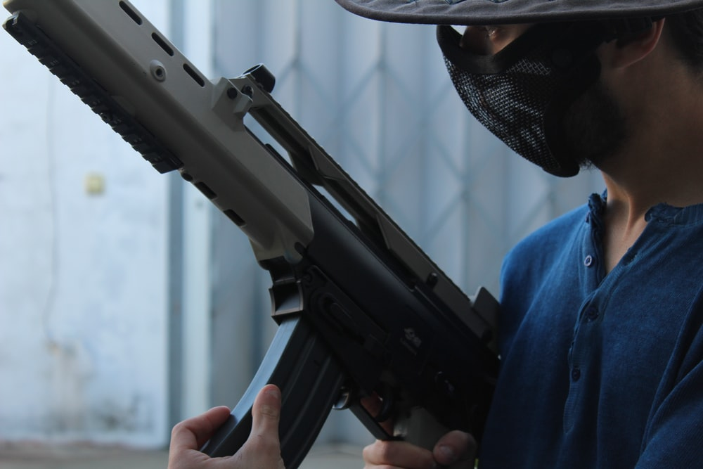 person holding assault rifle