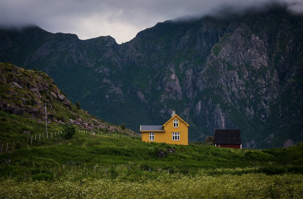 yellow wooden house near mountain during cloudy day