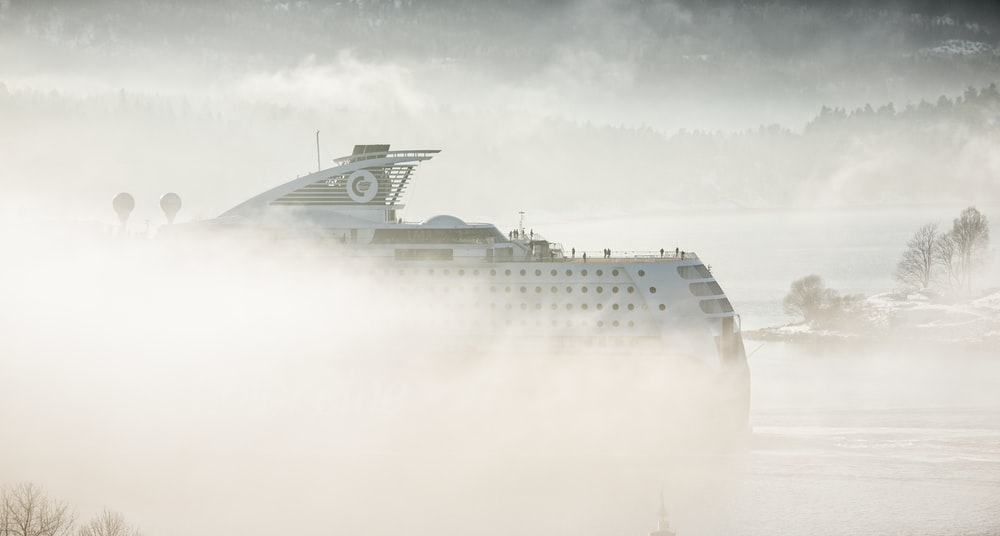 white cruise ship covered in mist
