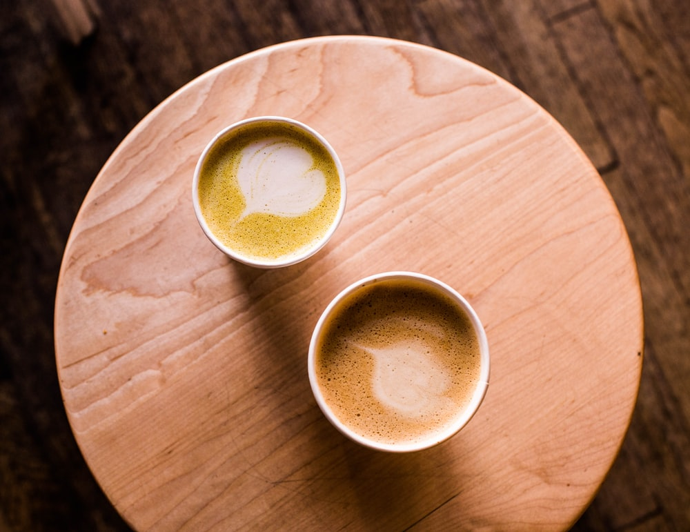 two beige cappuccinos on beige wooden stool