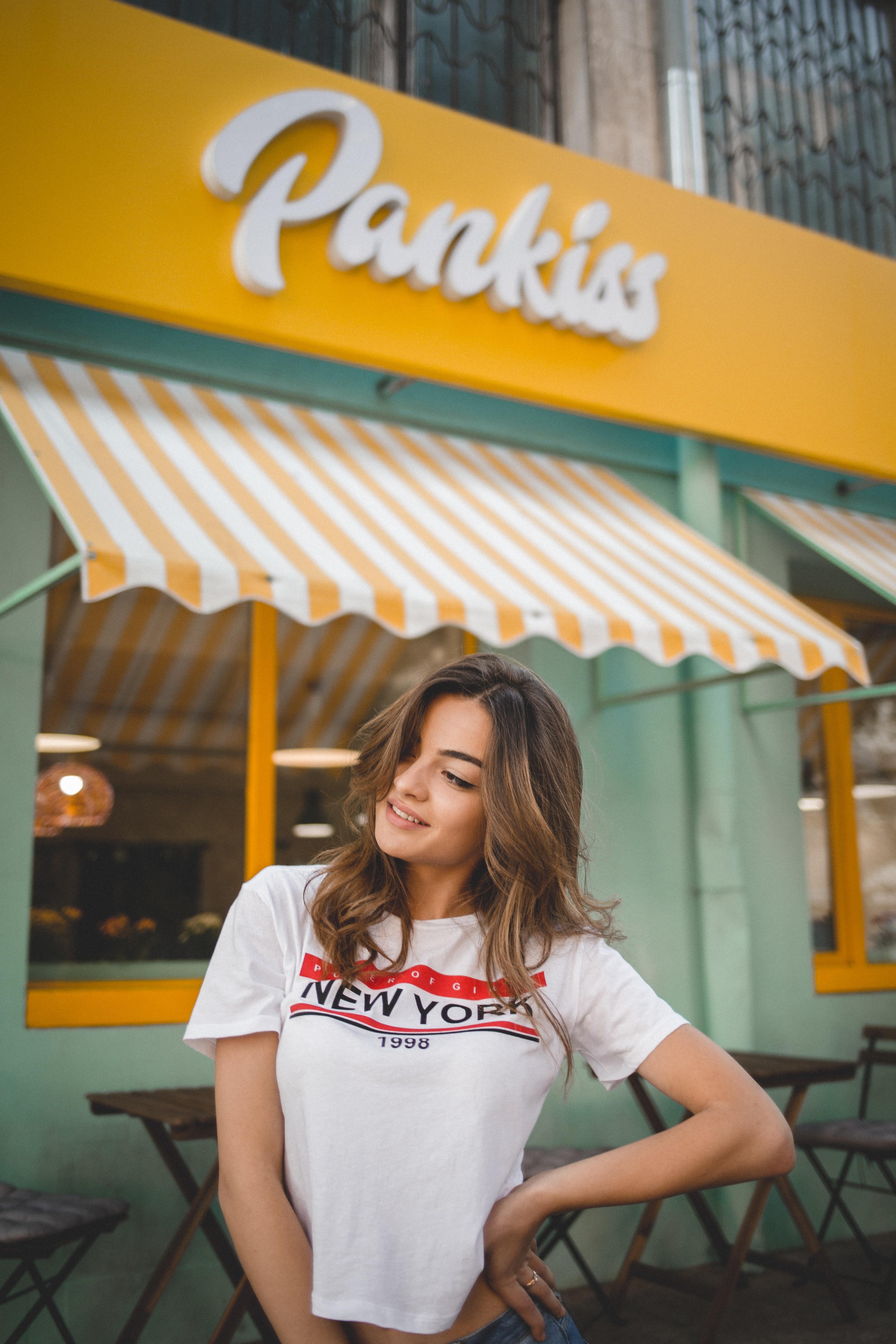woman wearing white t-shirt standing near Pankiss facade