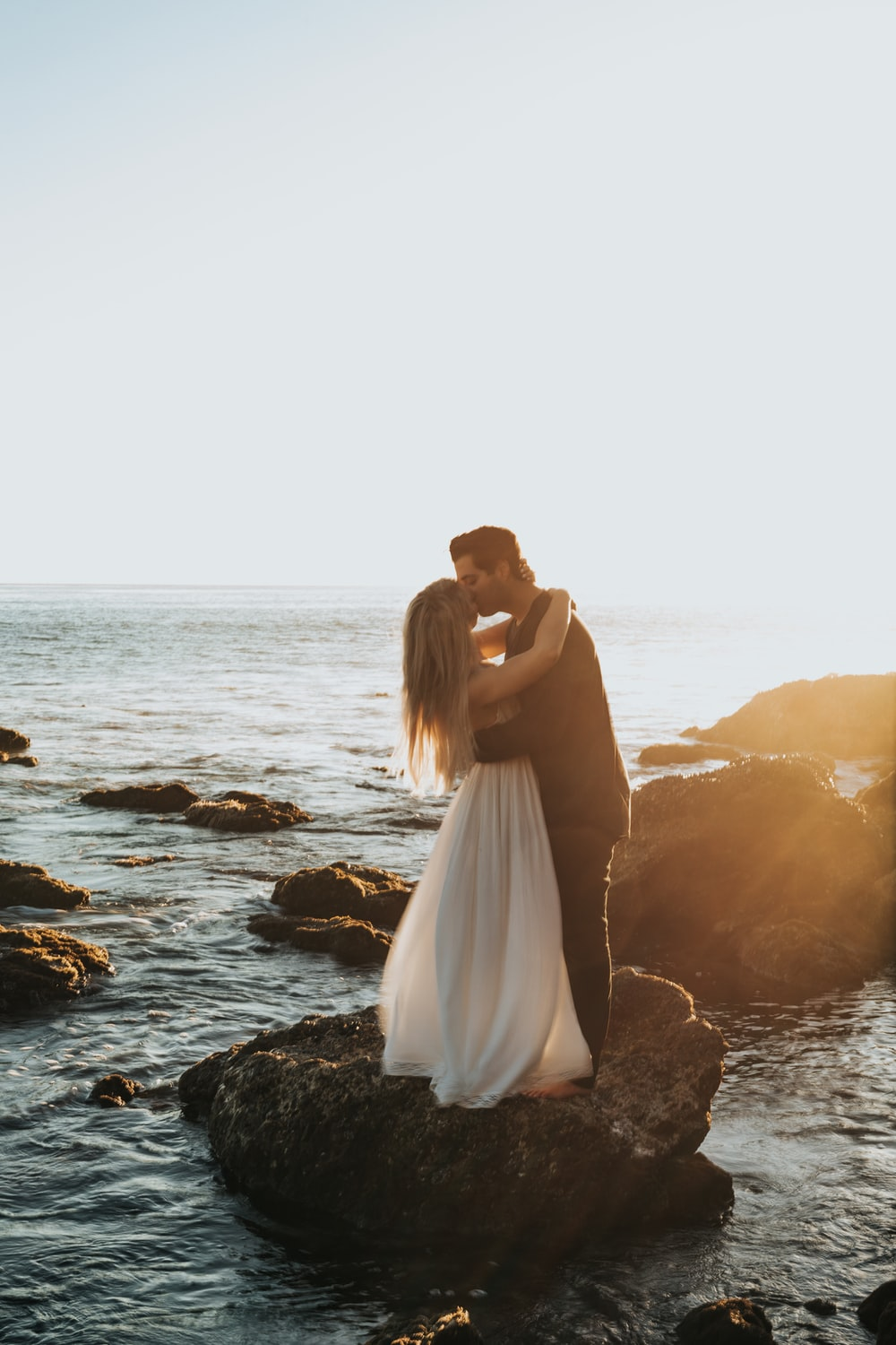 man and woman kissing on top of gray rock at beach