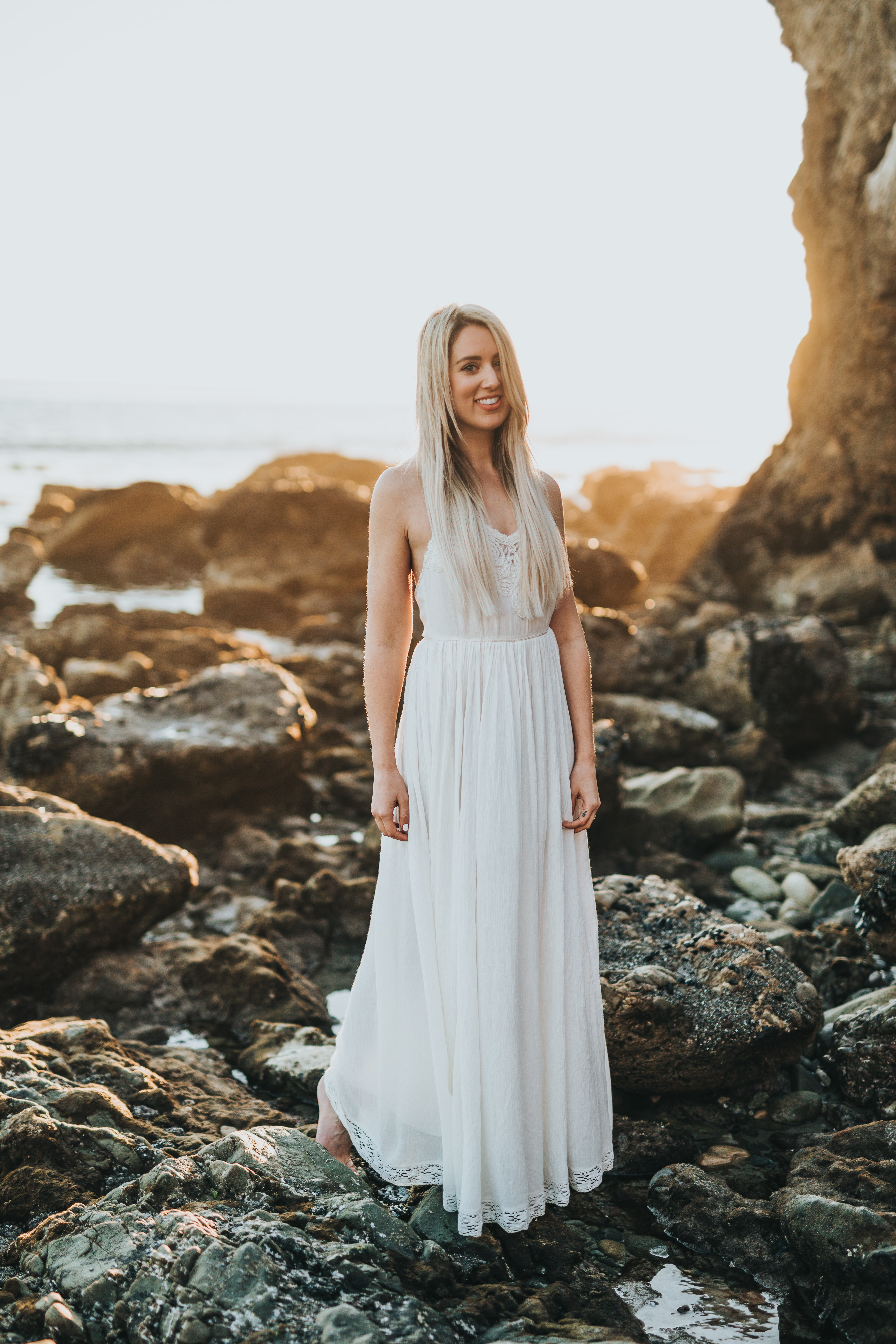 selective focus photography of woman standing at sea rock formation