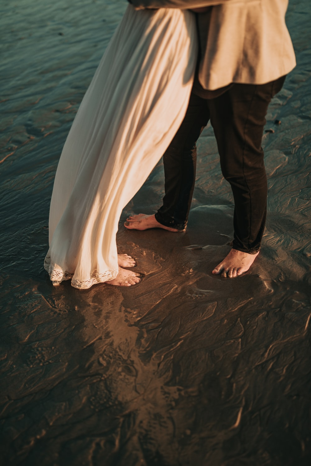 man and woman standing shallow body of water