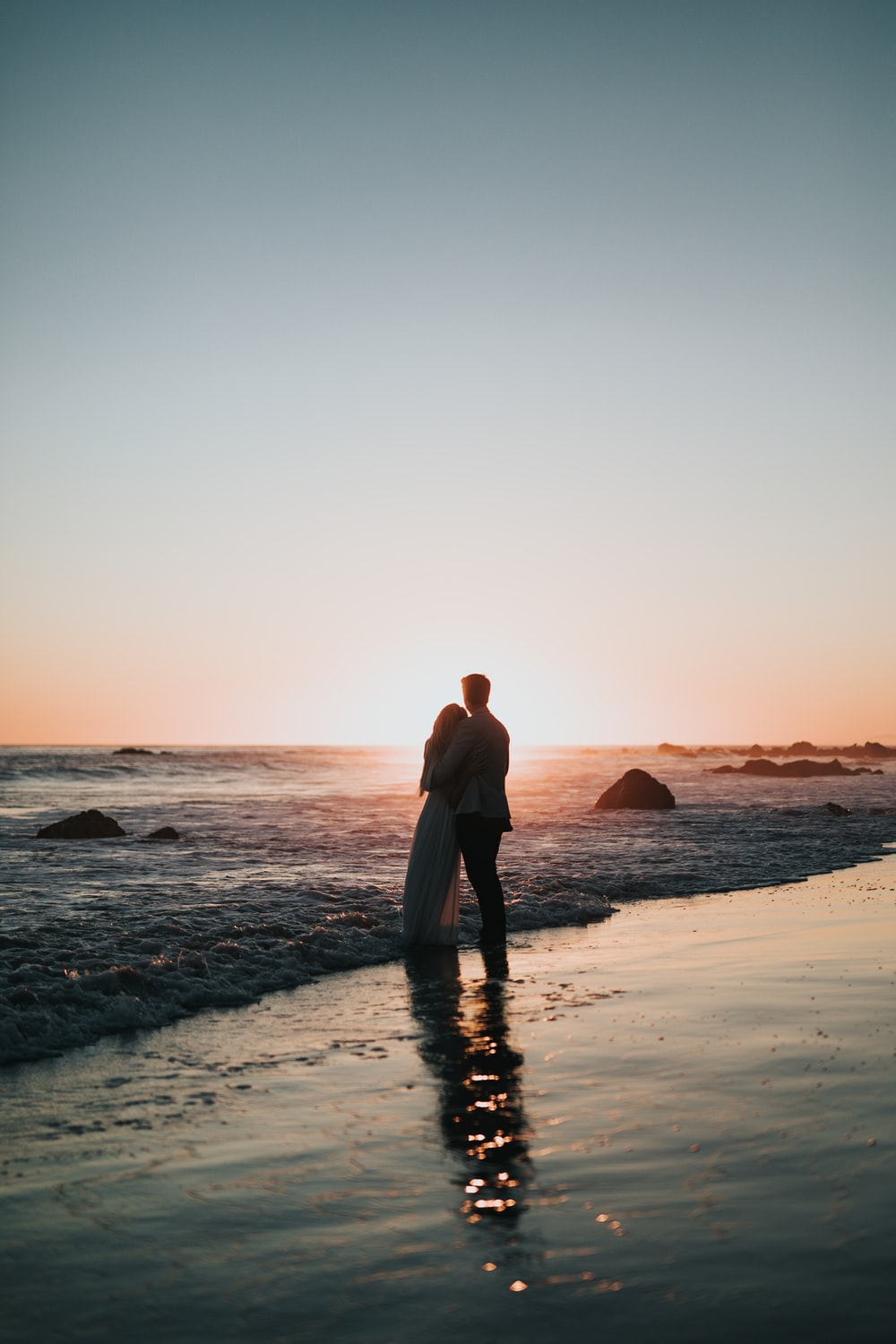 silhouette photo of couple standing on beach watching sunset