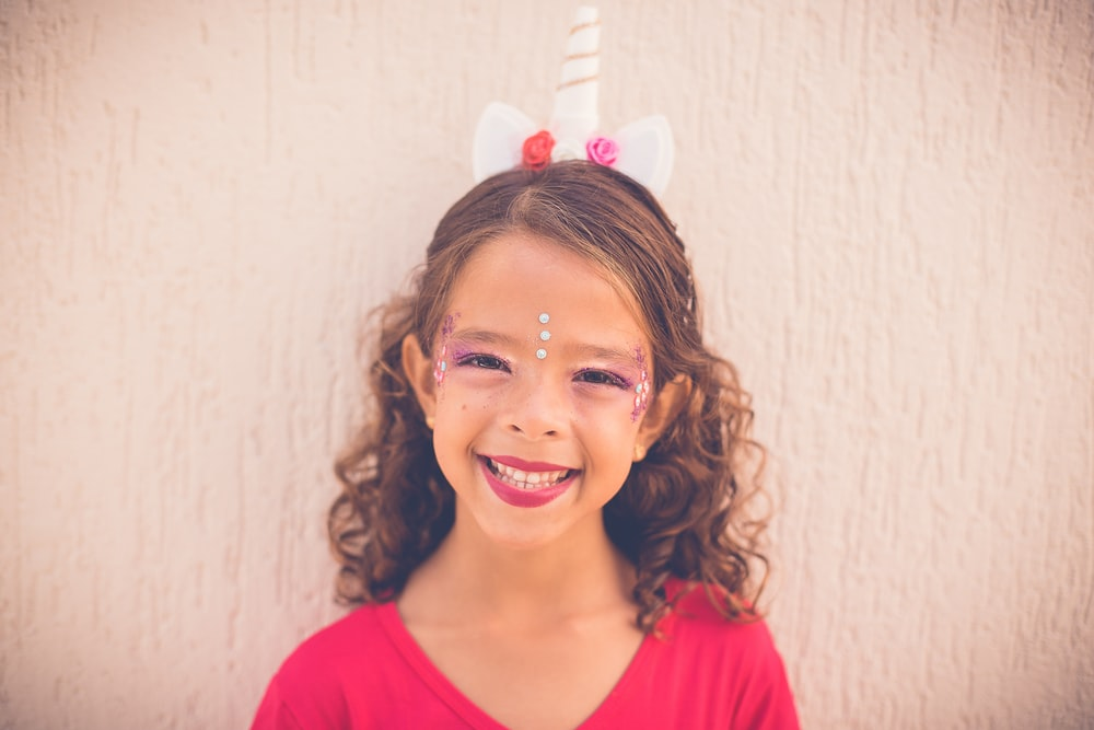 closeup photo of smiling girl wearing red top