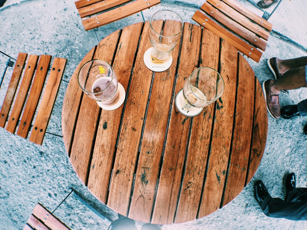 flat-lay photography of empty pint glasses on top of brown wooden slatted table