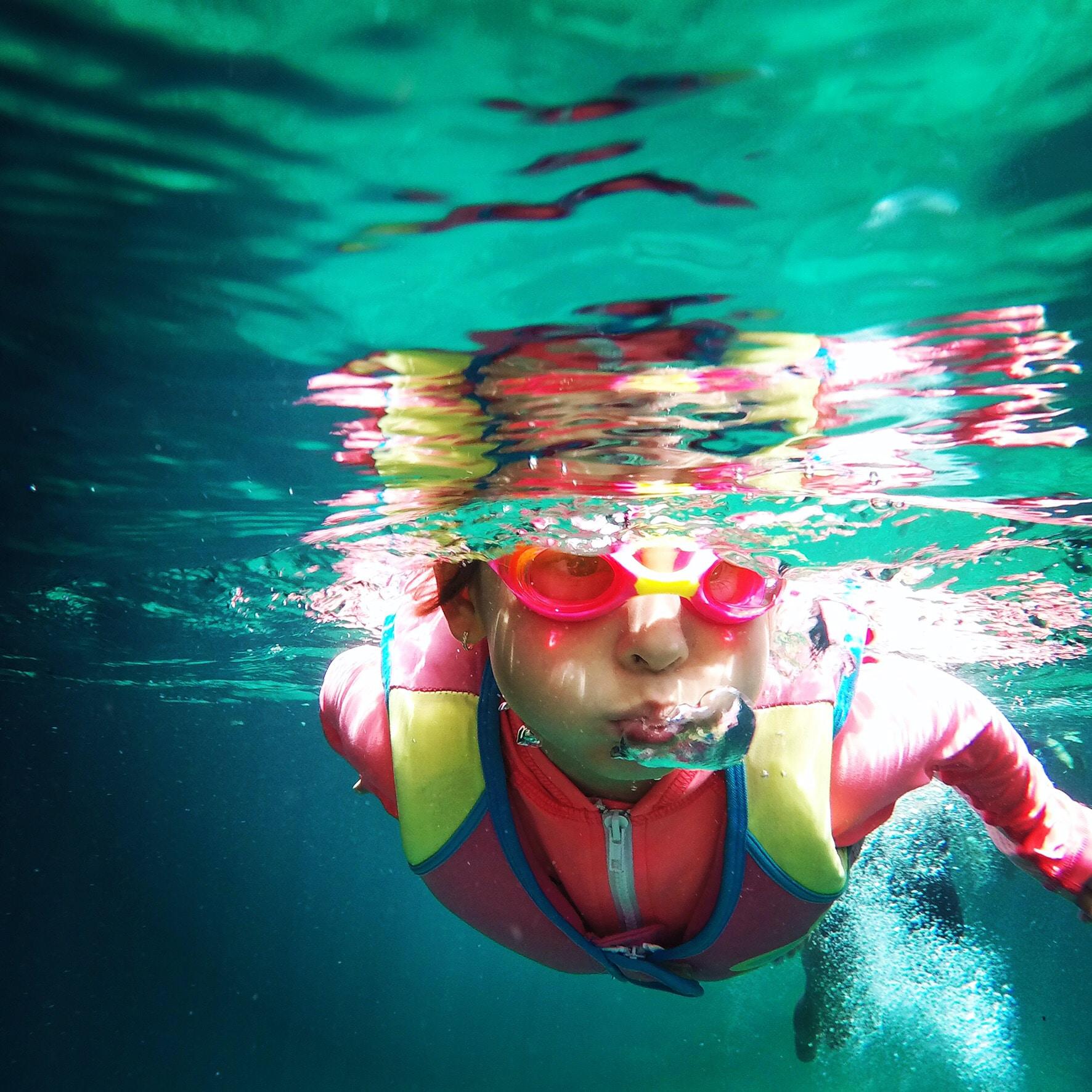 person in pink zip-up jacket swimming under water - home school activity