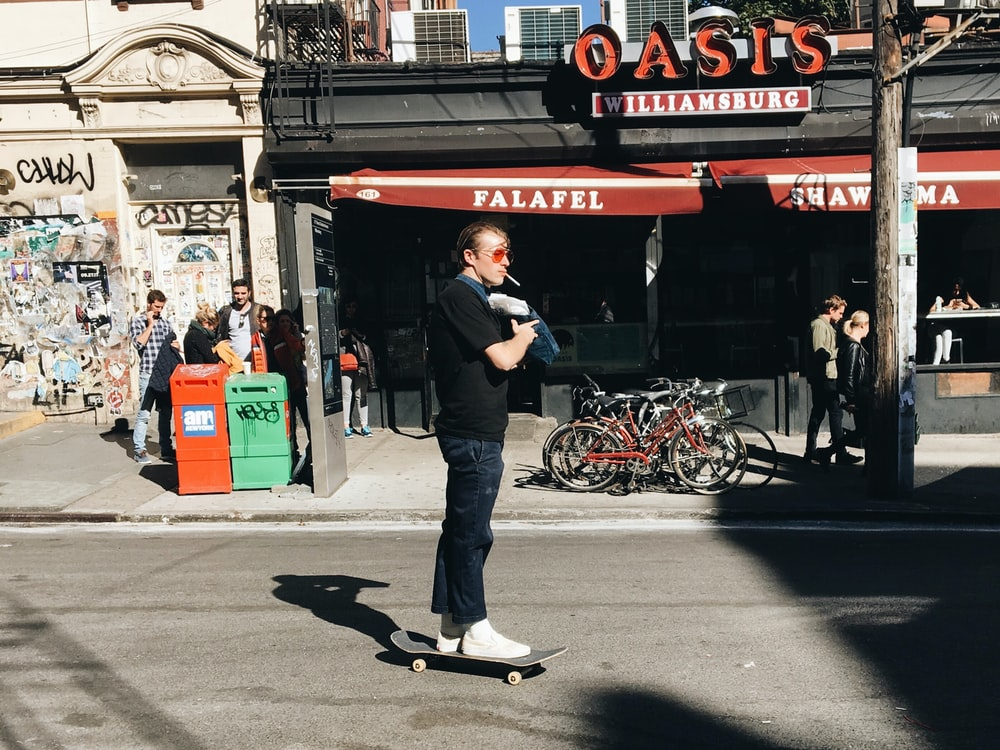 man riding skate near gray and red building during daytime