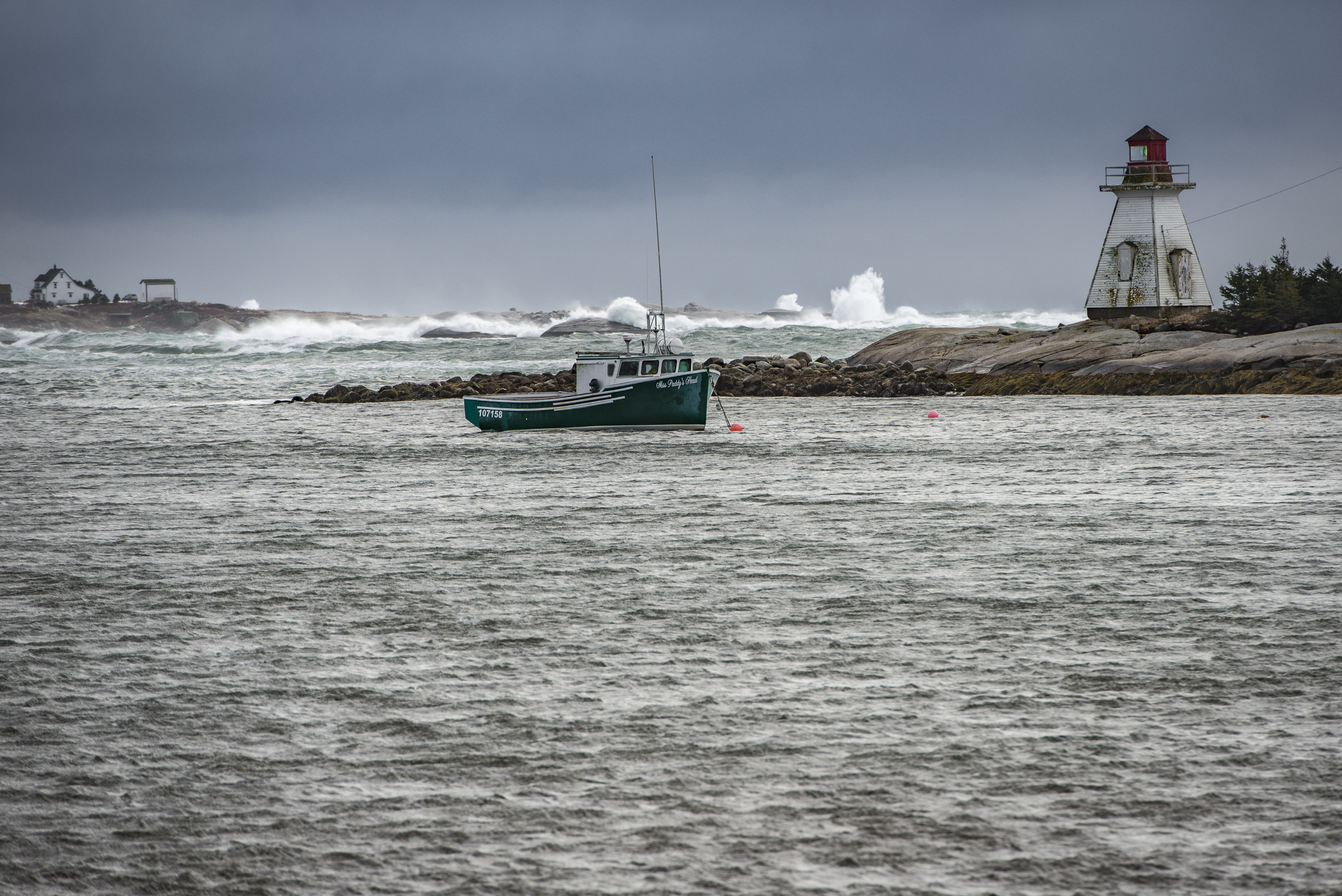 teal boat on body of water near lighthouse