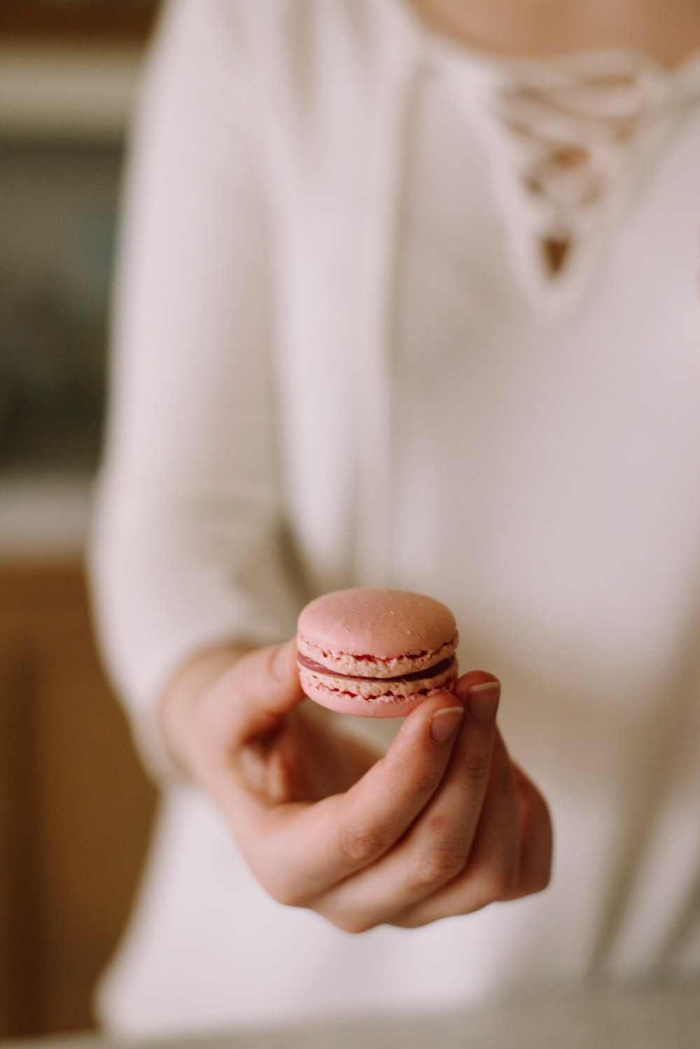 person holding pink macaroon