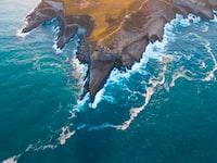 bird's eye photography of mountain near ocean