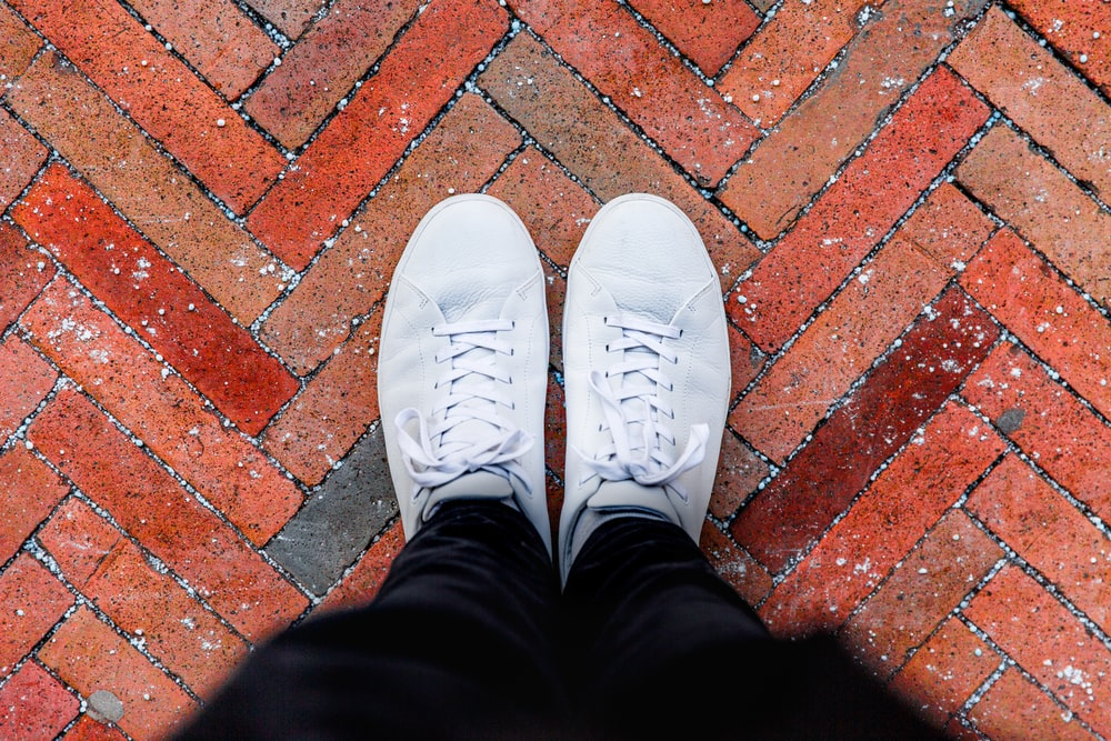 person wearing white sneakers standing on top of brown brick ground