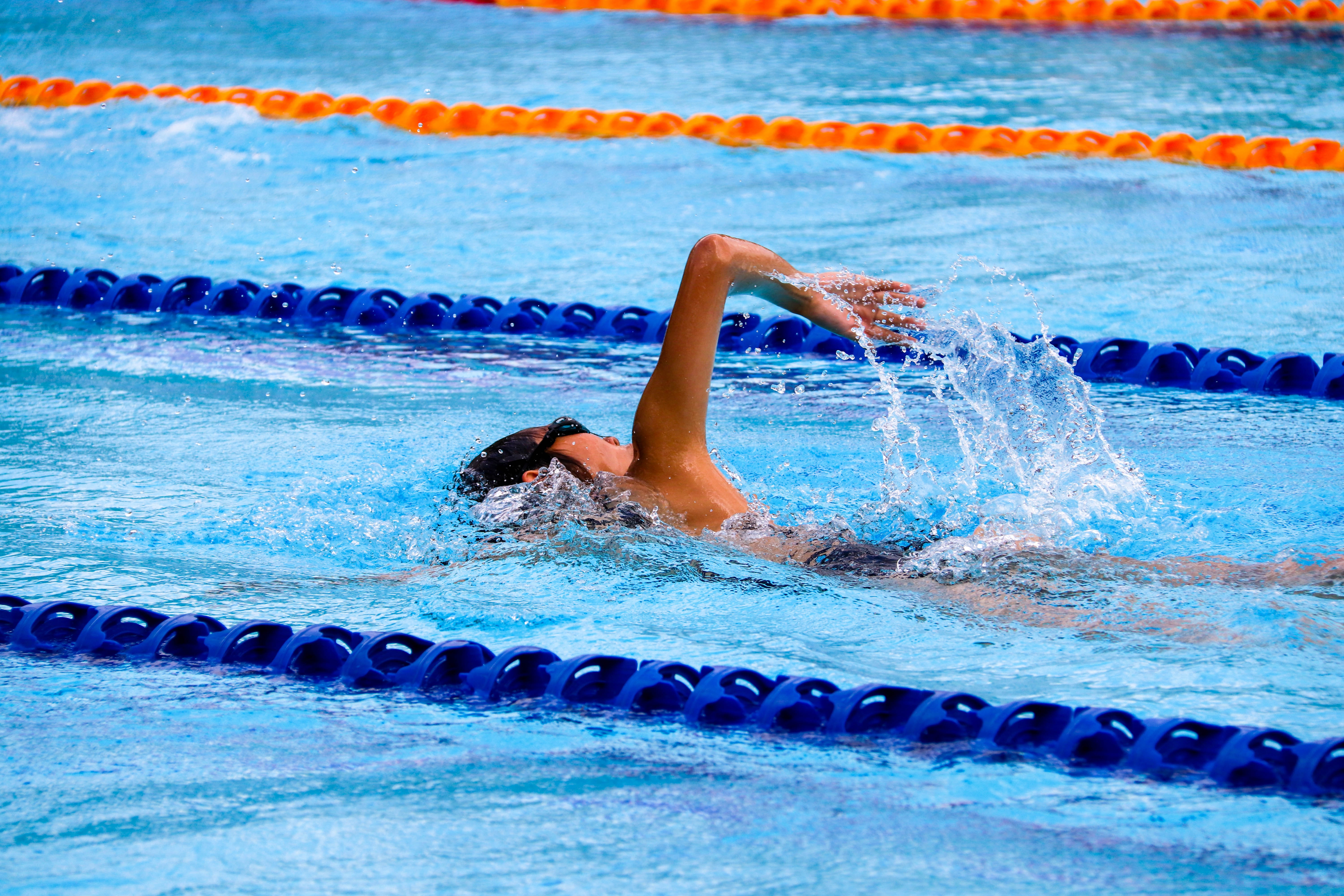 person swimming on an olympic pool