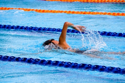 person swimming on an olympic pool swimming teams background