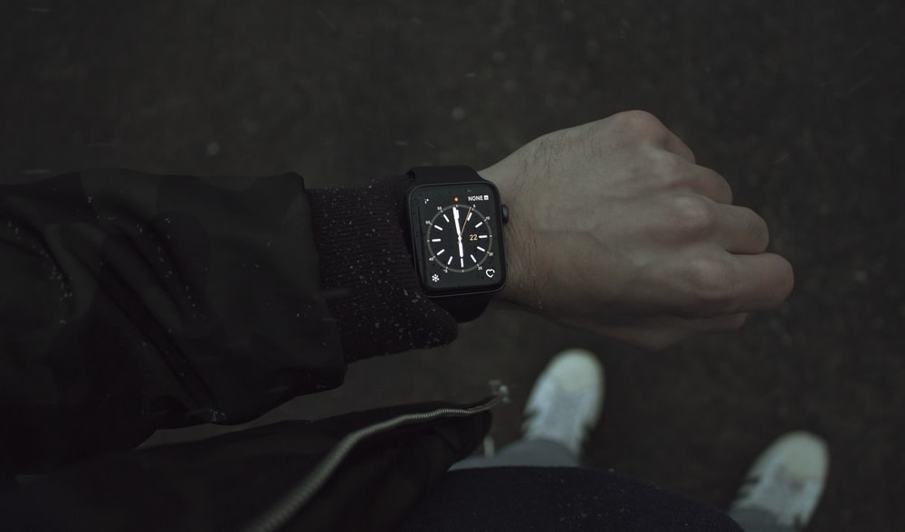 person wearing space black Apple Watch with black strap