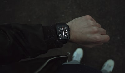 person wearing space black apple watch with black strap device zoom background