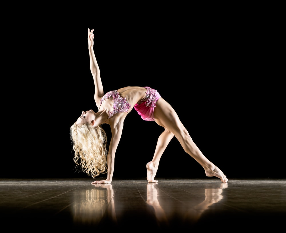 woman bending on floor and with black background
