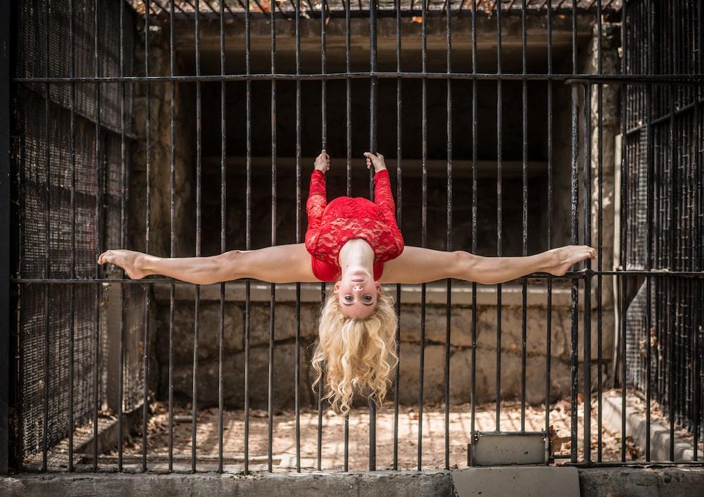 woman bending her legs on metal cage