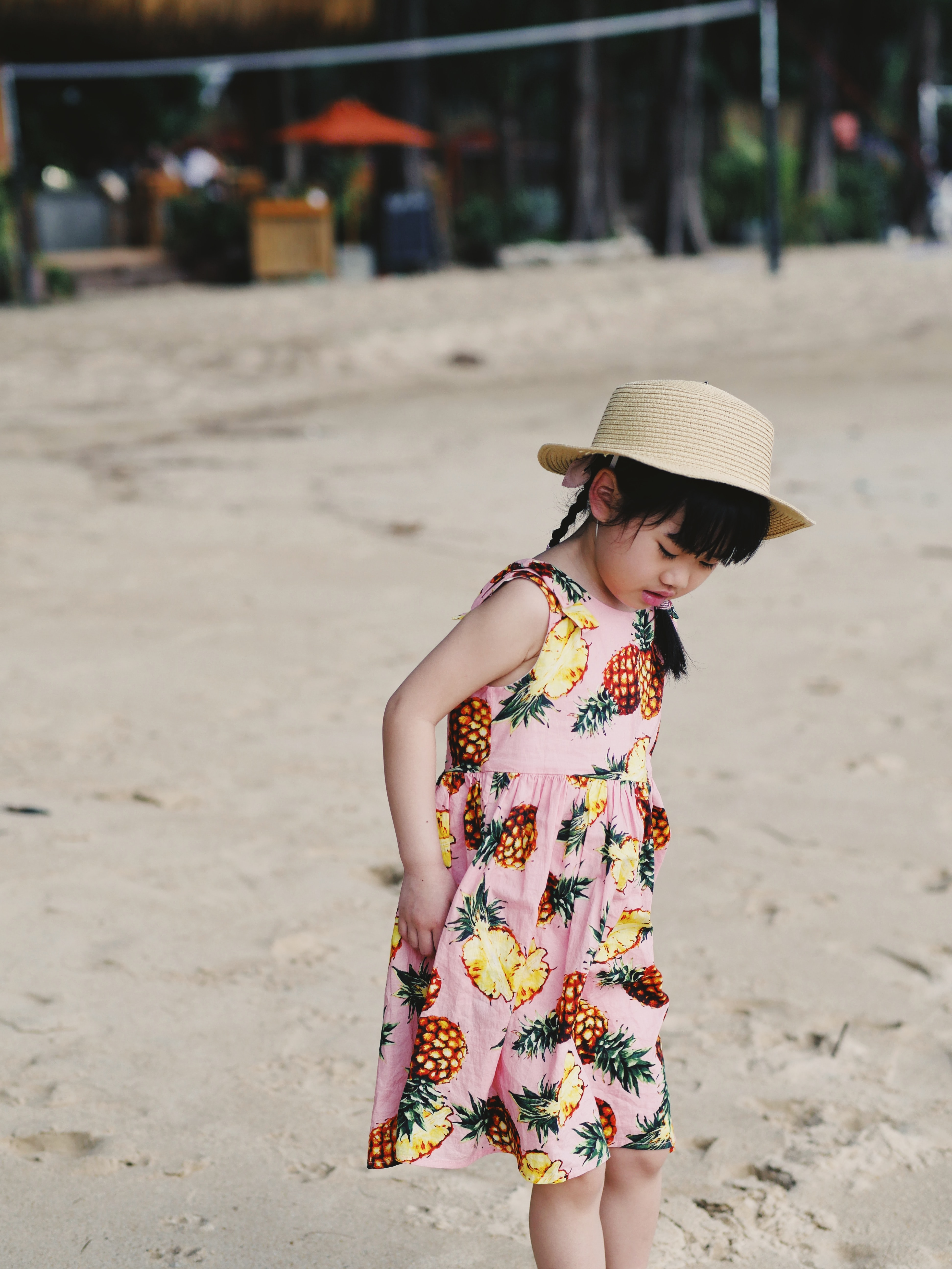 girl wearing pink dress standing on sand