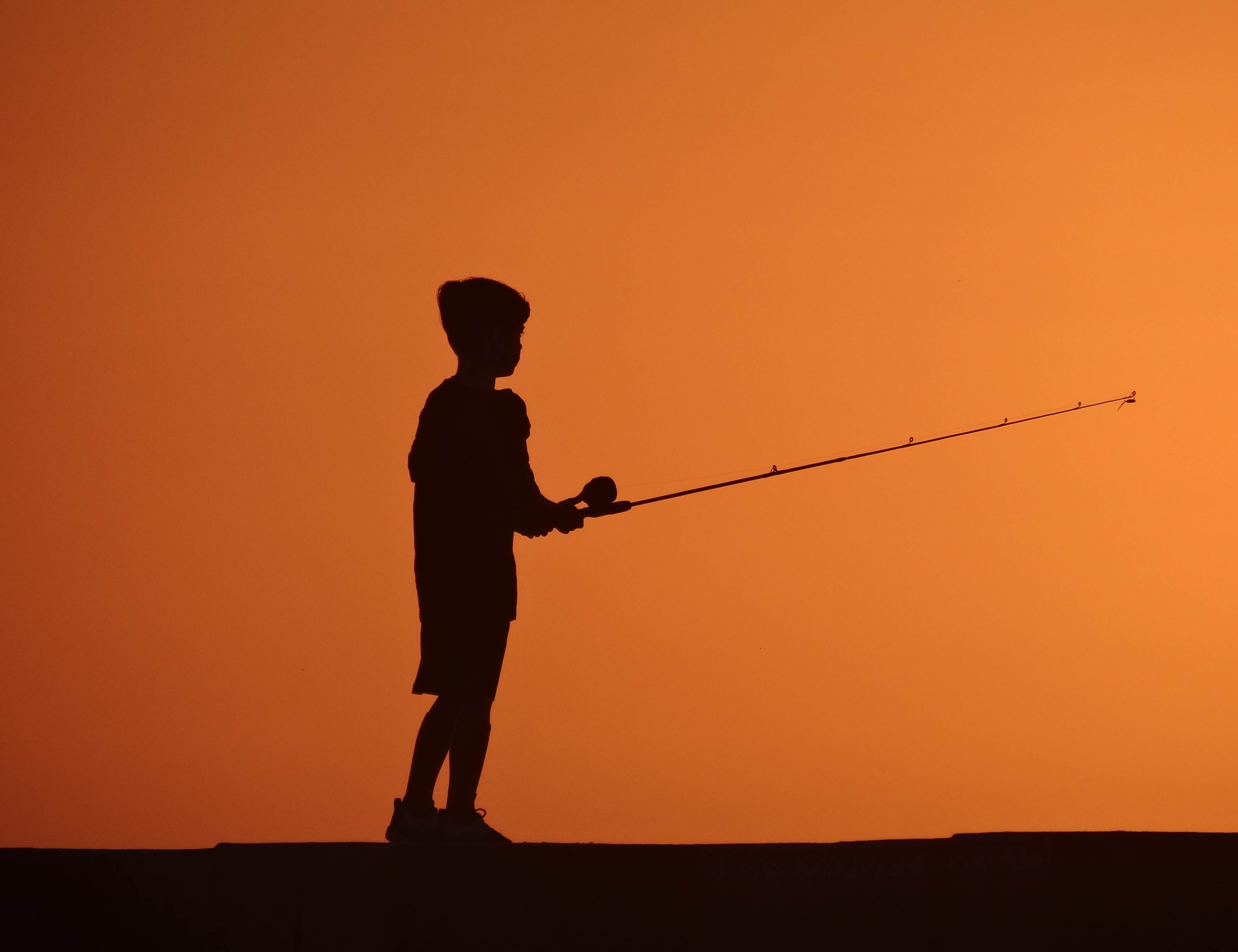 silhouette photo of boy fishing during sunset