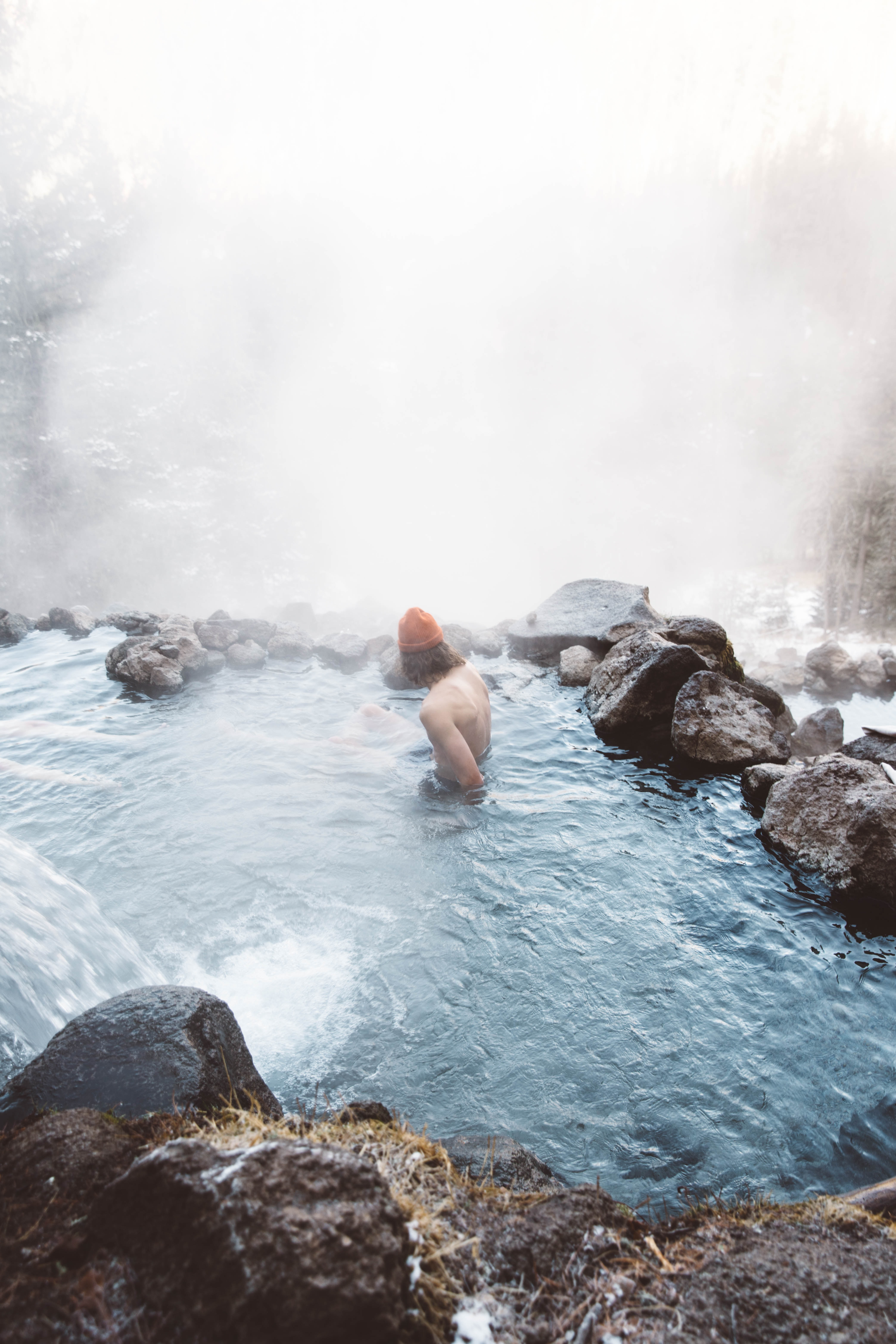 man sitting in water with fog during daytime