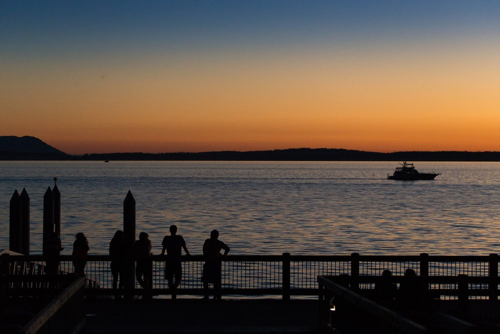 silhouette of people standing on dock during sunset