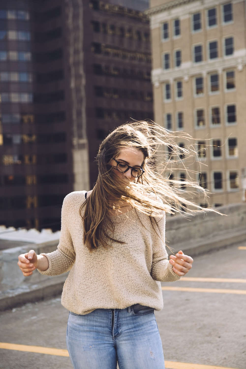 woman standing near building with hair being blown by wind