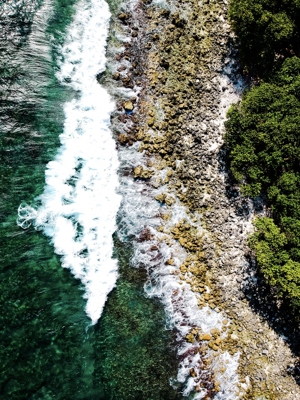 top-view photo of seawater with bubbles on rocks