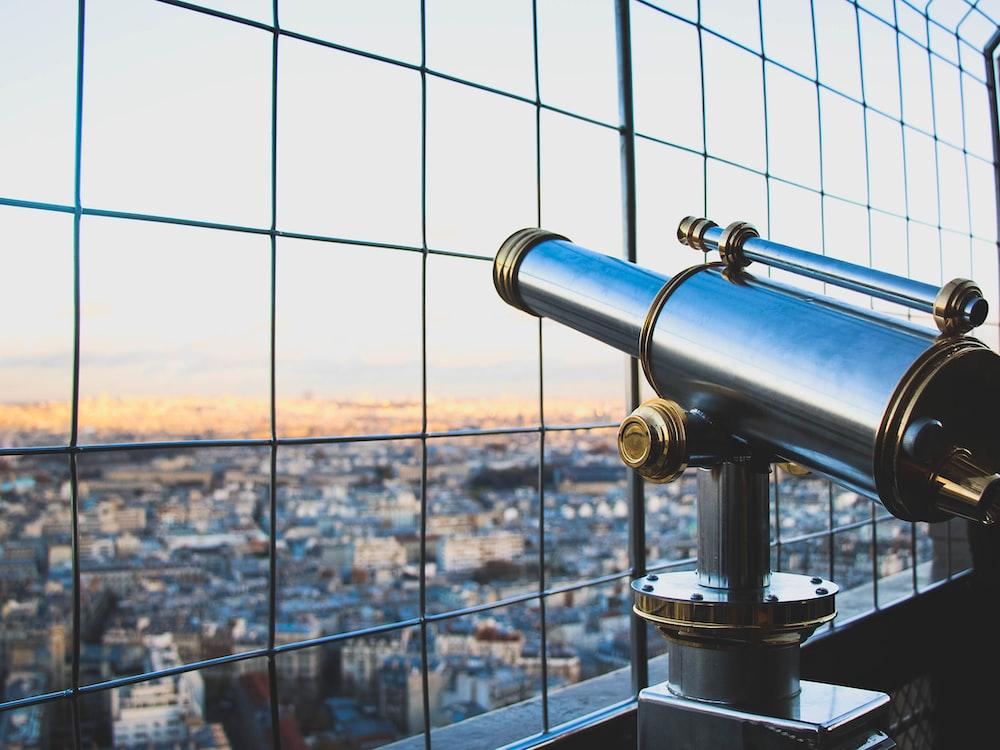 silver telescope near fence