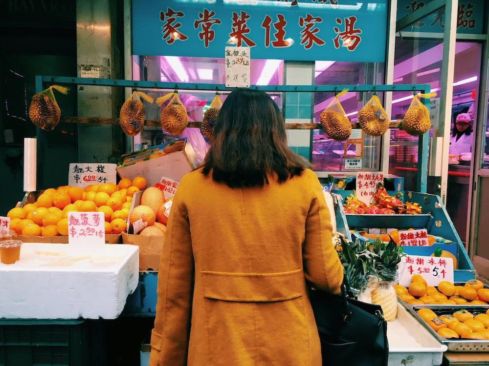standing woman wearing brown coat toward display fruits