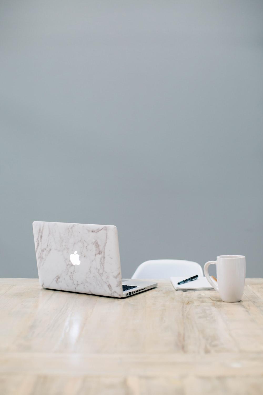 MacBook on table near mug