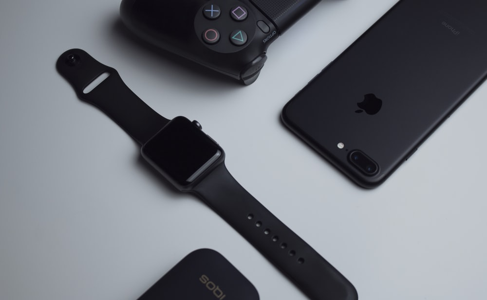 black iPhone 7 Plus and space gray Apple Watch with black sport band