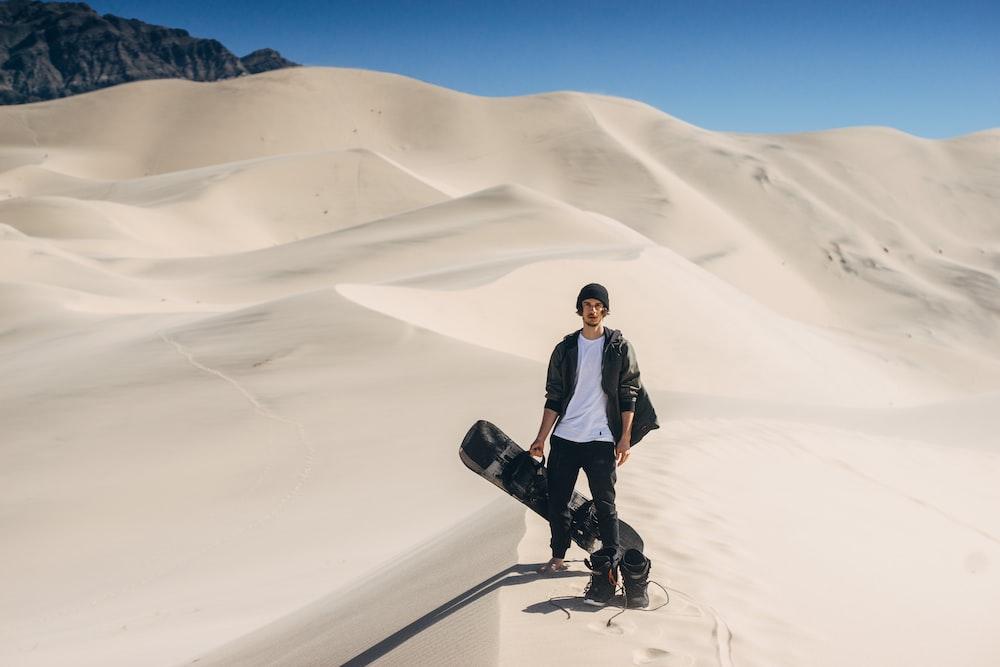 man in black jacket standing on desert
