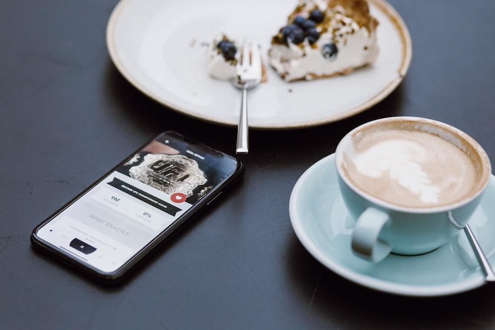 teal ceramic teacup on saucer beside black smartphone