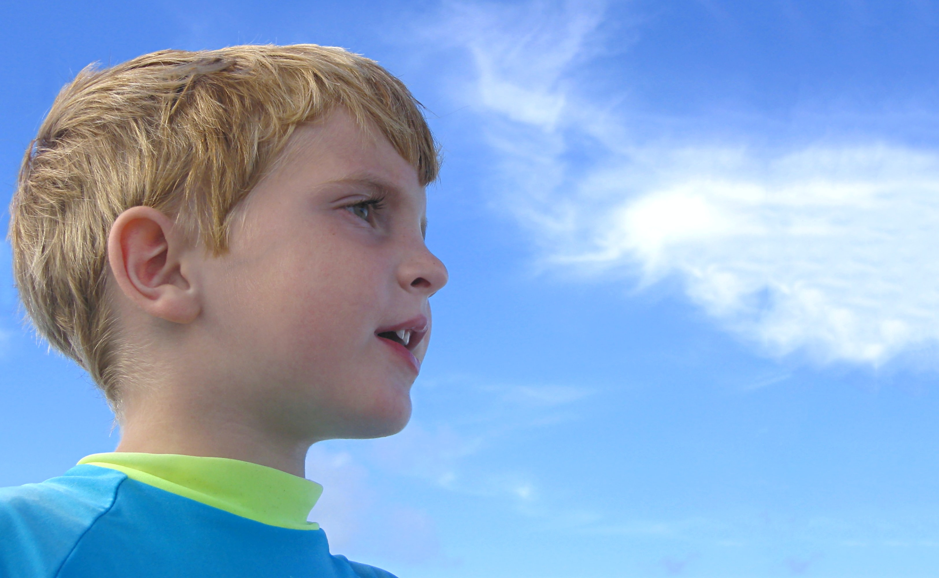 blonde haired boy wearing blue shirt under white and blue cloudy skies