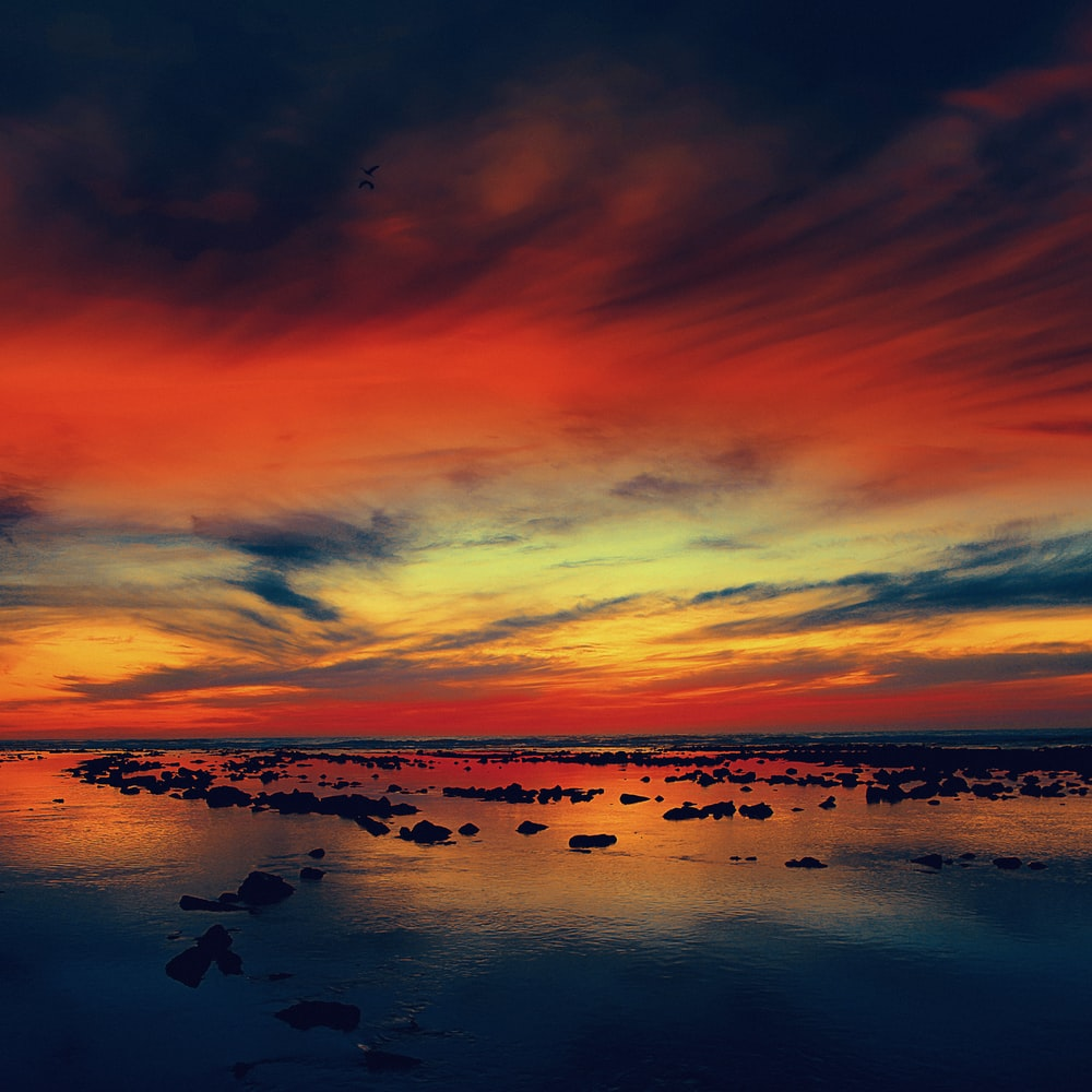 silhouette of rocks on body of water under red and blue clouds