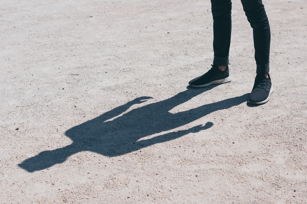 person in black skinny jeans standing on the field