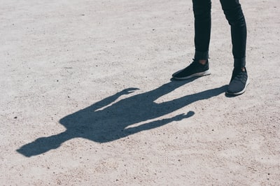 person in black skinny jeans standing on the field shadow zoom background