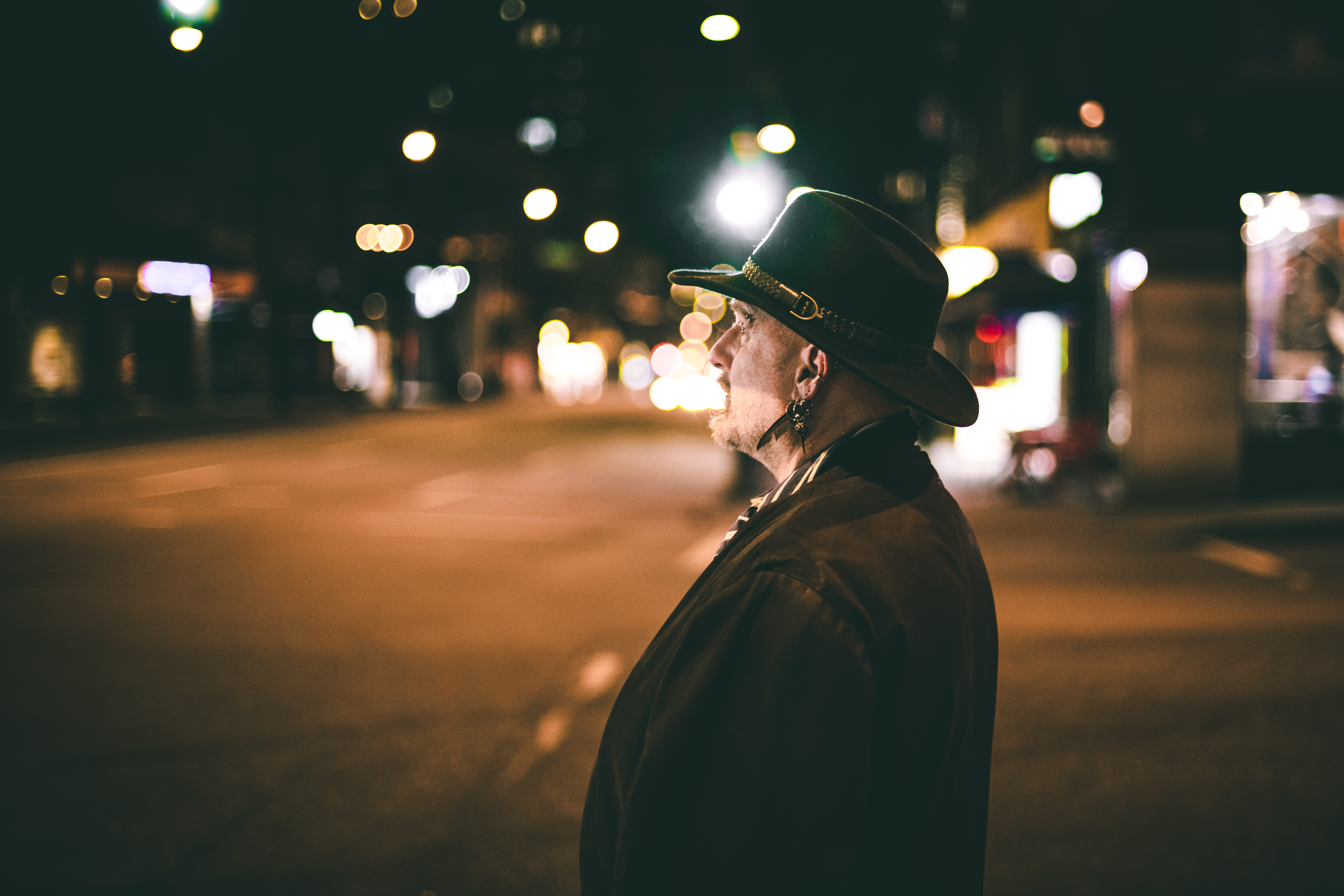 man standing on roadside at night time