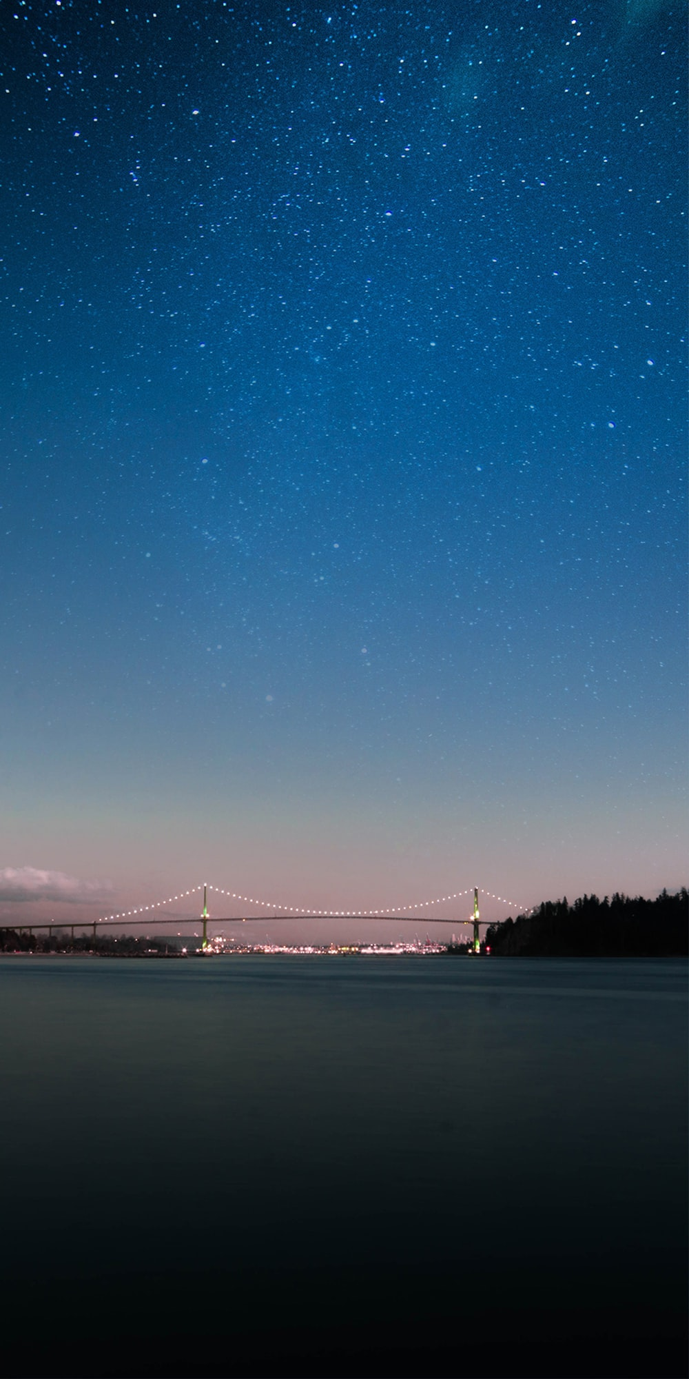 lighted bridge under blue and white sky at night