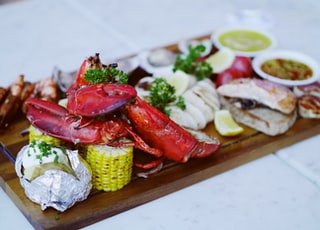 cooked lobsters on brown wooden serving tray with sauce