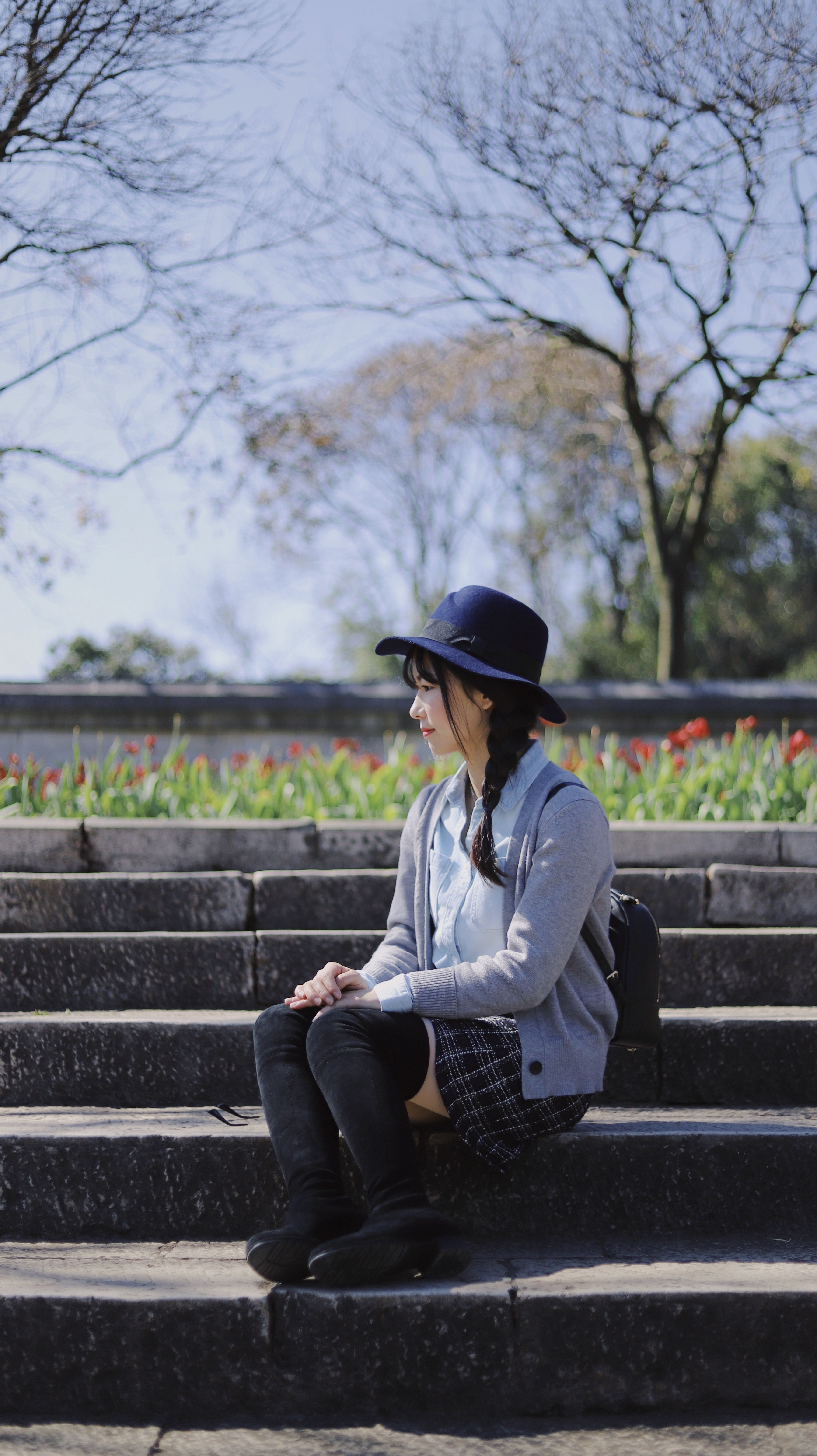 girl sitting on concrete staircase outdoor during daytime