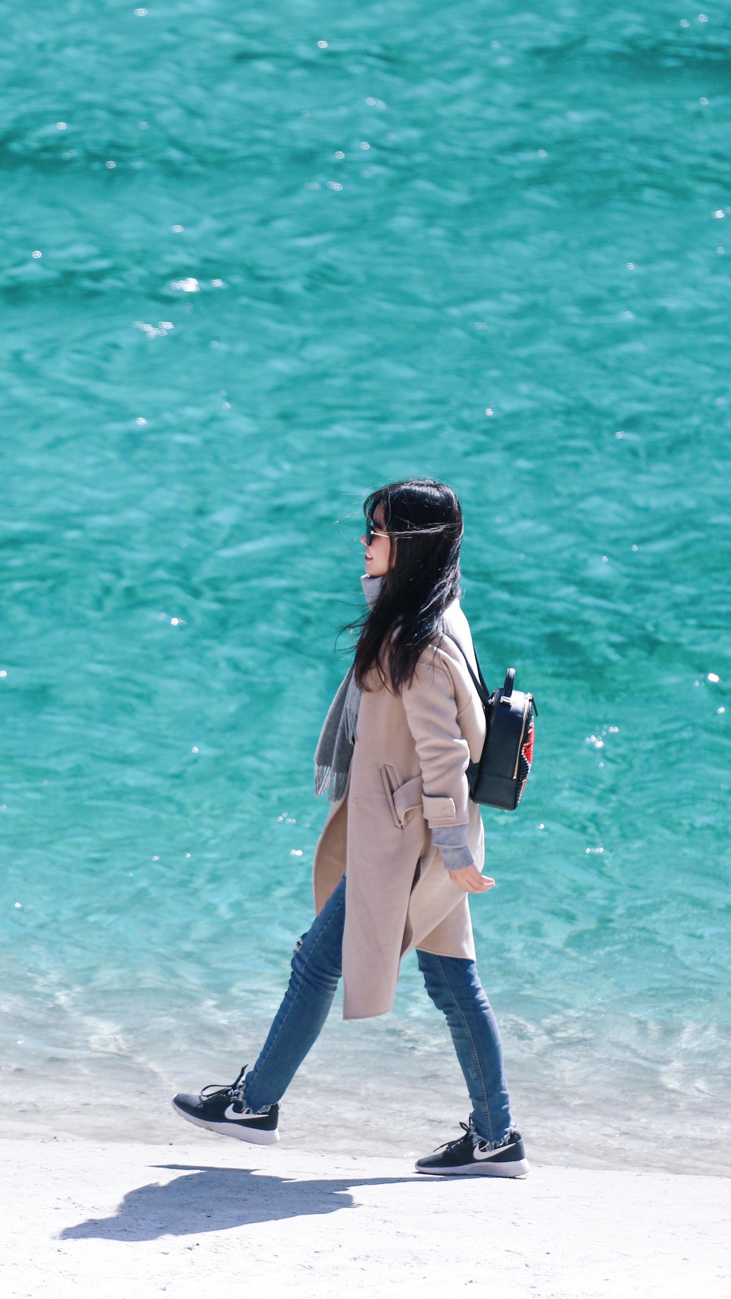 woman walking on seashore wearing coat