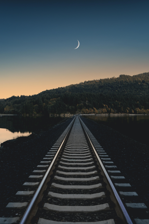 railroad towards mountain under blue sky