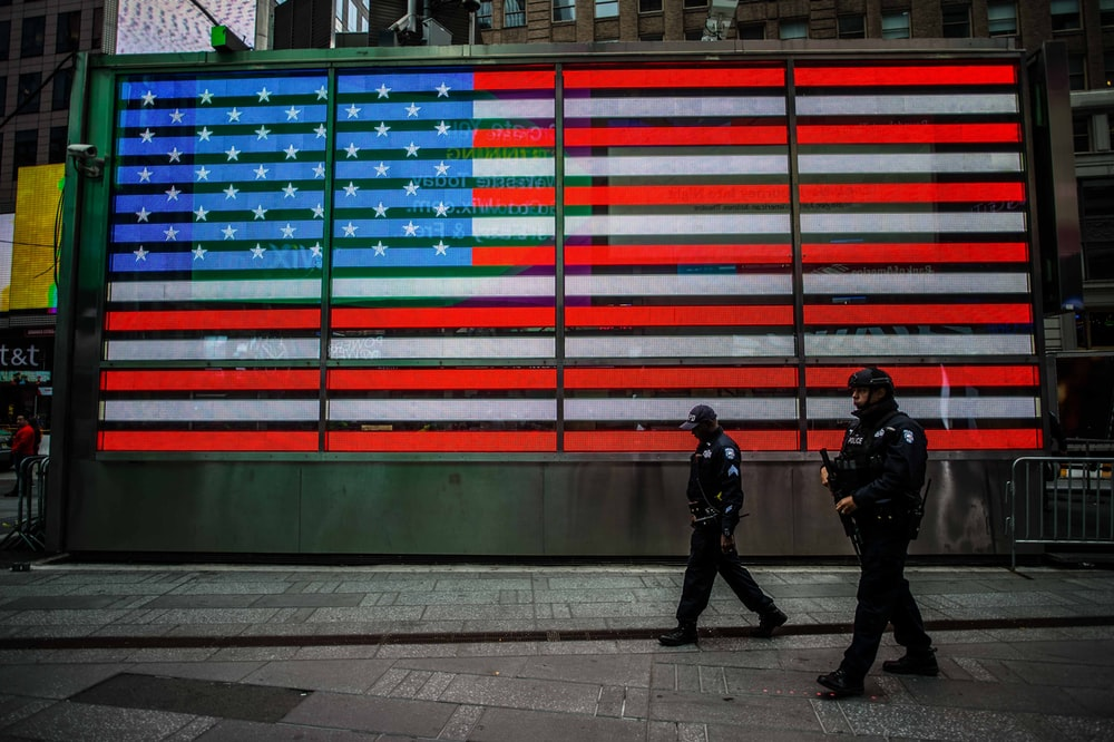 two man walks near USA flag wall