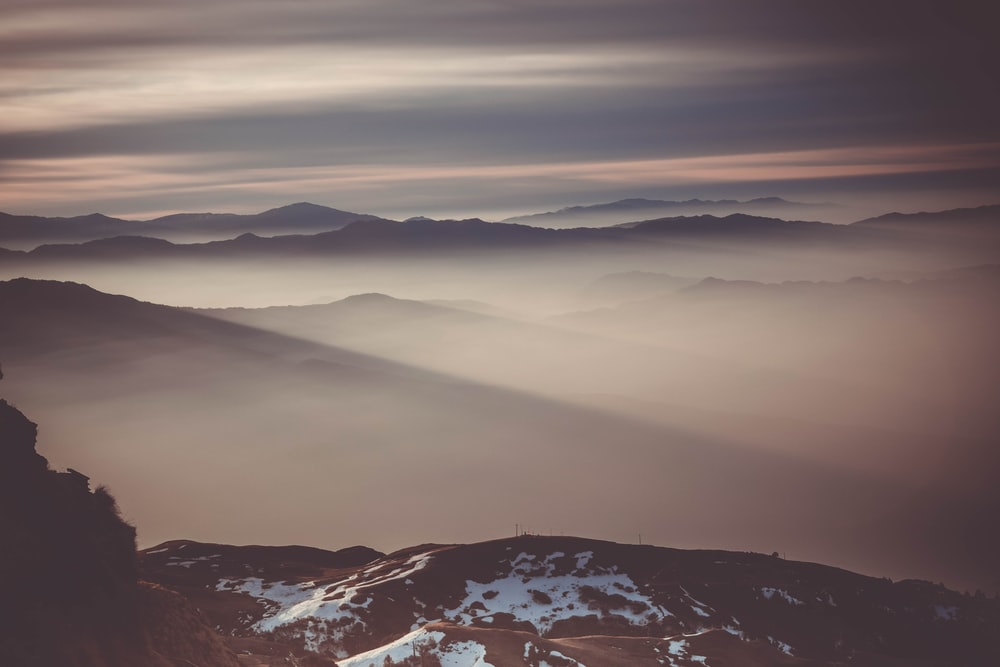 fogs at mountains during golden hour