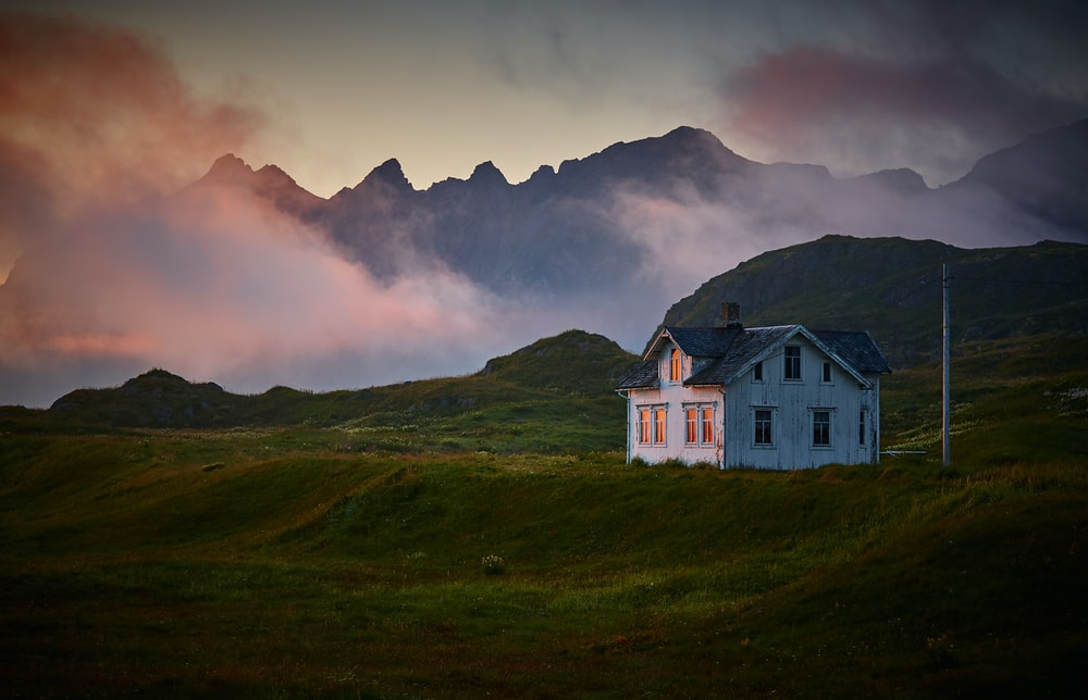 white and gray house near mountain under cloud